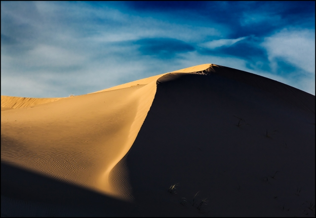 The golden light of late afternoon starts to rake across the dunes helping the sand stand out from the deep blue of the sky and clouds that echo the wind-blown shapes.  Canon 5D Mk II w/ 70-200mm f4L