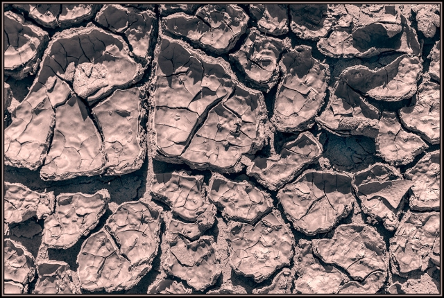 Pattern of mud crust cracked and baking in the sun.