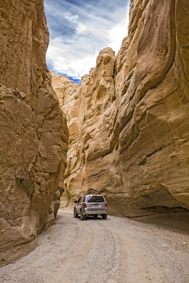 Canyon walls dwarf the little SUV as the canyon becomes narrower and narrower.  Click on Image to enlarge.