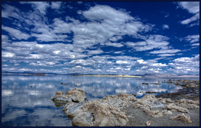 Mono Lake shoreline.  THe small deposits of tufa seem to mirror the clouds in the sky and reflected in the calm water.