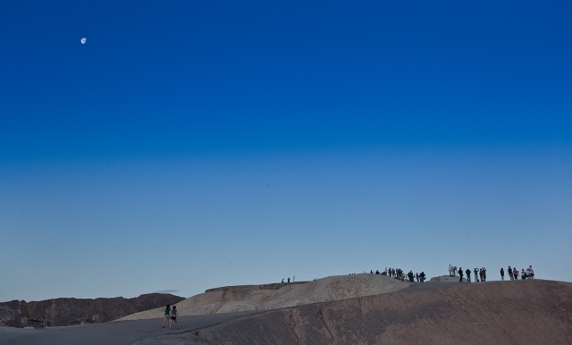 The moon watches as photographers take their positions awaiting the dawn light to illuminate Manley Beacon and the Panamint Mountain Range from Zabriski Point, Death Valley