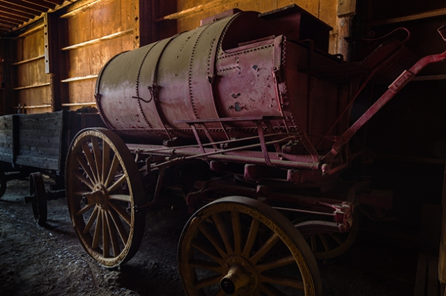 """Old water wagon stuck back in the corner of a barn at the museum.  This is a """"Straight"""" shot of it.  Canon 5D MkII with 24mm f1/4 TS/E and the light coming in from the foors to the barn."""