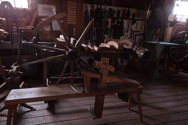 original shot of wheelwright station in the blacksmith barn at the museum as seen thourhg the closed grating doors.