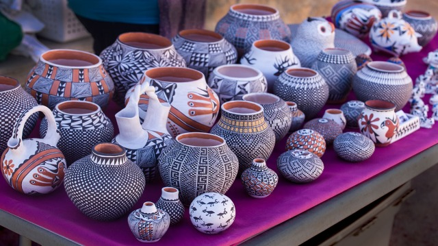 """It was early morning but a vendor had already set a table with her pottery for the day's visitors.  Acoma pottery is known for the delicate lines forming complex patterns around the piece.  A """"polychrome"""" style it often has other colors in the designs."""