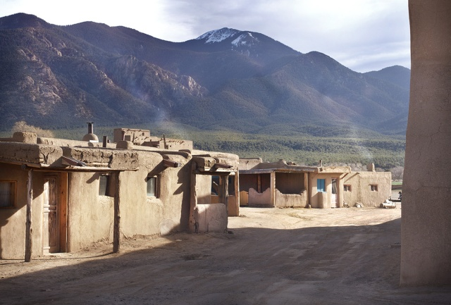 Morning light on a Taos Pueblo street with cook-fire smoke and the sacred Taos Mountain in the background.  You can see some of the rock outcroppings sparkling in the morning light.  Canon 5D MkII