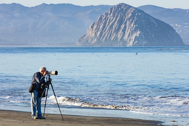 Photographer Lee Peterson on the beach at Cayucos in front of Morro Rock