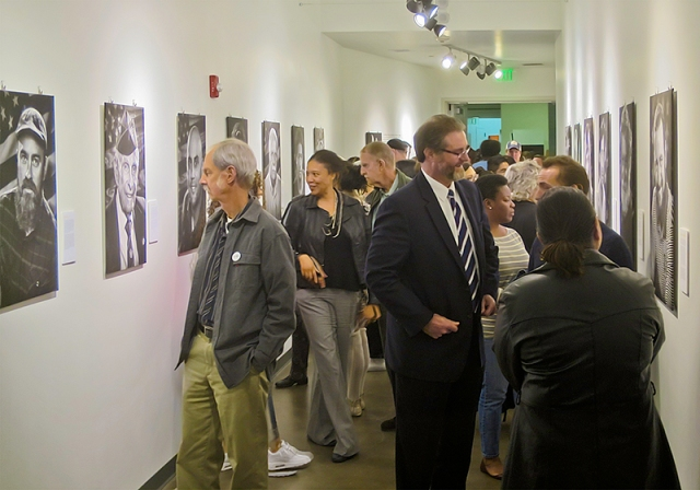 "The entrance hallway to the gallery during the opening of the ""Voices: Honoring Veterans"" show.  Just to the right of center in the dark suit is College President Anthony Beebe talking with one of the student veterans by their portrait."