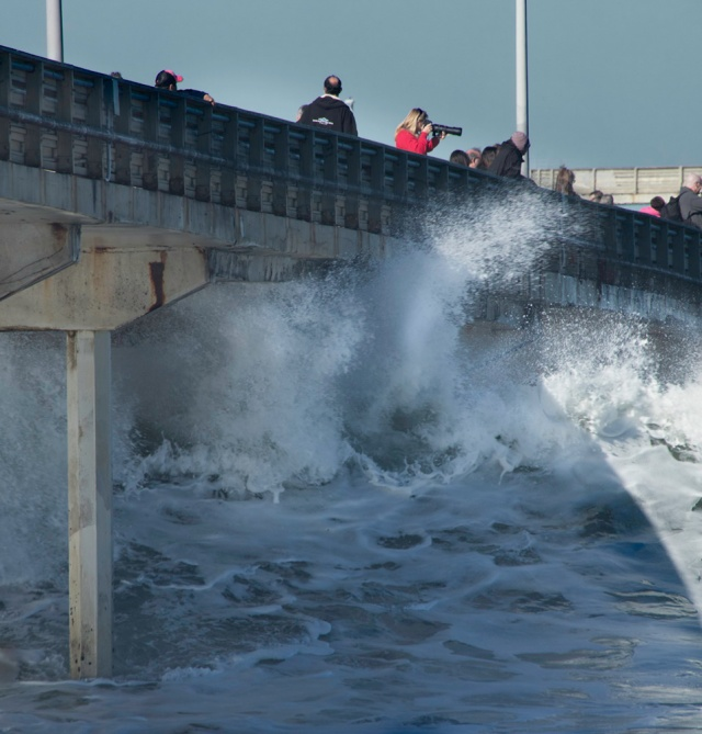 As the water shoots and sprays under the pier, Cynthia is photographing surfers trying to ride the foam. She is in the red sweater with the camera more or less in the top center of the shot.