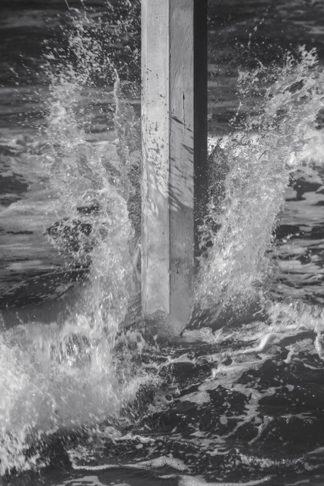 Detail shot of a small wave, most of its energy spent further out, breaking against one of the pilings close to shore.