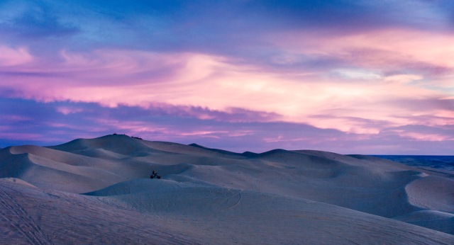 ATV riders find high dunes to watch the sunset from the Imperial Dunes near Glamis, CA